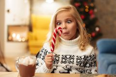Close-up portrait of curious little girl holding and looking at. Big candy cane while sitting at the table on Christmas morning Stock Images