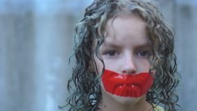 Close up portrait of a curly sad teenager girl with her mouth taped over with red tape. Violation of freedom of speech stock video footage
