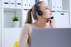 Close-up portrait of a customer service agent sitting at office propped her head by hand and dreaming. royalty free stock images
