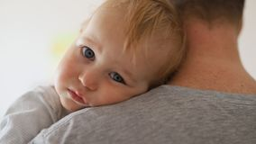 Close-up portrait of cute adorable blond caucasian toddler boy on fathers shoulder indoors. Sweet little child feeling. Safety on daddys hand. Responsibility stock video