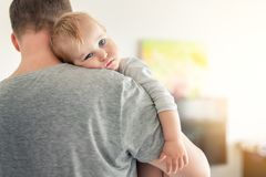 Close-up portrait of cute adorable blond caucasian toddler boy on fathers shoulder indoors. Sweet little child feeling safety on royalty free stock photography