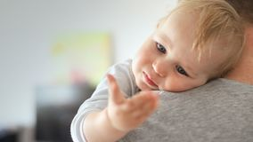 Close-up portrait of cute adorable blond caucasian toddler boy on fathers shoulder indoors. Sweet little child smiling. Feeling safety on daddys hand stock footage