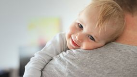 Close-up portrait of cute adorable blond caucasian toddler boy on fathers shoulder indoors. Sweet little child smiling. Feeling safety on daddys hand stock video footage