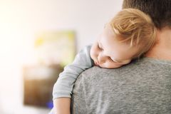 Close-up portrait of cute adorable blond caucasian toddler boy sleeping on fathers shoulder indoors. Sweet little child feeling royalty free stock photo