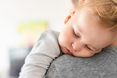 Close-up portrait of cute adorable blond caucasian toddler boy sleeping on fathers shoulder indoors. Sweet little child feeling royalty free stock images