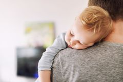 Close-up portrait of cute adorable blond caucasian toddler boy sleeping on fathers shoulder indoors. Sweet little child feeling royalty free stock photos