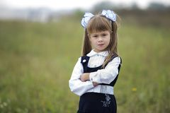 Close-up portrait of cute adorable confident first grader girl in school uniform and white bows in long blond hair on blurred. Light green sunny outdoors copy royalty free stock image