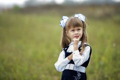 Close-up portrait of cute adorable confident first grader girl in school uniform and white bows in long blond hair on blurred. Light green sunny outdoors copy royalty free stock photos