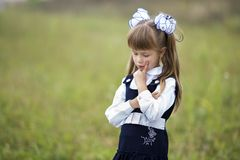 Close-up portrait of cute adorable confident first grader girl in school uniform and white bows in long blond hair on blurred. Light green sunny outdoors copy stock photography
