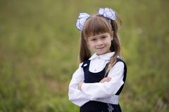 Close-up portrait of cute adorable smiling confident first grader girl in school uniform and white bows in long blond hair on. Blurred light green sunny stock image