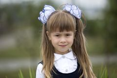 Close-up portrait of cute adorable smiling little first grader girl in school uniform and white bows in long blond hair on blurred. Light green copy space royalty free stock photography