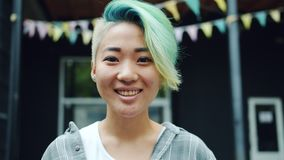 Close-up portrait of cute Asian hipster with dyed hair and nose piercing outside. Close-up portrait of cute Asian hipster with dyed hair and nose piercing stock video footage