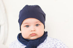 Close up portrait of cute baby boy wearing blue hat. Stock Image