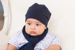 Close up portrait of cute baby boy wearing blue hat. Stock Photos