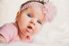 Close-up portrait of cute baby girl in pink lying down on a white bed. Looking at camera. Big open eyes. Healthy little Royalty Free Stock Photography