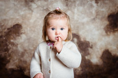 Close-up portrait of cute blond little girl with big grey eyes. And plump cheeks keeping her finger in her mouth. Studio portrait on grunge background Royalty Free Stock Images