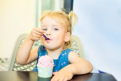 Close up portrait of cute blondy toddler baby girl eating berry ice-cream from paper bowl in cafe. Taste and childhood concept. He stock photography