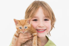 Close-up portrait of cute boy holding kitten. On white background Royalty Free Stock Photo