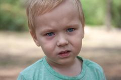 Close up portrait of cute caucasian baby boy with serious expression in blue eyes. stock image