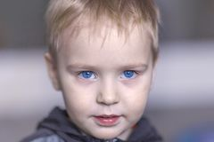 Close up portrait of cute caucasian baby boy with very serious face expression. Bright blue eyes, fair hair. Strong emotions. royalty free stock photos
