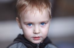 Close up portrait of cute caucasian baby boy with very serious face expression. Bright blue eyes, fair hair. Strong emotions. stock image