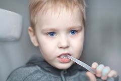 Close up portrait of cute caucasian baby boy with very serious face expression cleaning the teeth with teeth brush, by himself. Br stock images