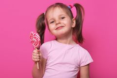 Close up portrait of cute child wearing rose casual t shirt, happy little girl holding big sugar lollipop, has gladness facial. Expression charming, posing  on stock image