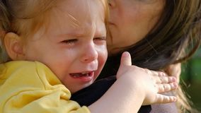 Close-up portrait of a cute crying little girl sitting in her mother arms stock footage