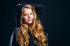 Smiling young girl. A close-up portrait of a cute emotional girl posing over the black background in studio. Beauty, fashion for kids and teenagers royalty free stock images