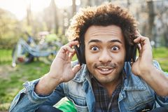 Close-up portrait of cute fashionable african-american, looking with popped eyes and lifting eyebrows at camera while. Sitting in park and listening music via Royalty Free Stock Photos