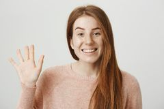 Close-up portrait of cute ginger girl waving with hand and smiling broadly at camera while standing over gray background. Singer met her mates from band and royalty free stock photos