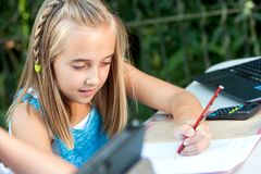 Cute girl doing schoolwork outdoors. Stock Photos