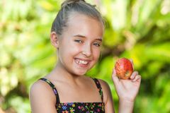 Cute girl holding red apple outdoors. Stock Photography