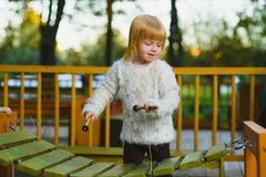 Close up portrait of cute girl playing xylophone outdoor Royalty Free Stock Photography