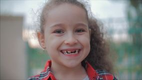 Close-up portrait of a cute happy Caucasian little girl making a surprised face and then smiling looking at the camera stock footage