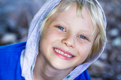 Close-up portrait of a cute happy child. Close-up, portrait of a cute smiling child looking up, in a hoodie royalty free stock image