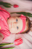 Close-up portrait of cute happy smiling baby girl lying down on pink bed with tulips around. Stock Images