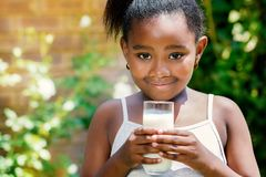 Sweet african girl holding milk glass outdoors. Stock Image