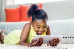 Little african girl playing on tablet in living room. Royalty Free Stock Photography