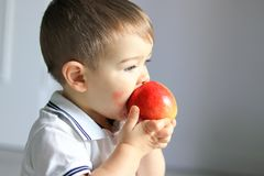 Close up portrait of cute little baby boy with atopic dermatitis on his cheek holding and eating red apple. royalty free stock image