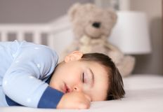Close up portrait of cute little baby boy in light blue pajamas sleeping peacefully on bed at home with soft teddy bear toy at bac royalty free stock image