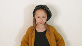 Portrait of little girl in black shiny hat and dress on white wall background. Close-up portrait of a cute little fashion girl in vintage shiny hat in the stock video footage