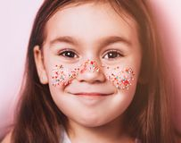 Close up portrait of Cute little girl with colorful topping on face on pink background. Easter child portrait, funny emotions, surprise. Copyspace for text stock image