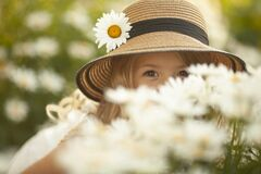 Close up portrait A cute little smiling girl in a straw hat peeks out of a chamomile bush.