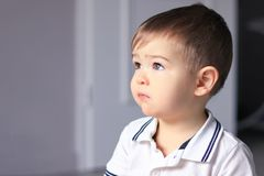 Close up portrait of cute little thoughtful baby boy in white shirt daydreaming at home. stock photos
