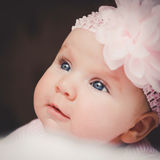 Close-up portrait of cute 3 months old smiling baby girl in pink. Big open eyes. Healthy little kid shortly after birth. Stock Photo