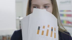 Close up portrait of cute playful young lady in formal clothes hiding her face behind papers looking in camera and away. Portrait of a cute playful young lady in stock video