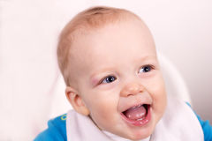Close up portrait of cute smiling baby boy in a child chair. Adorable laughing toddler. Stock Photo