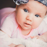 Close-up portrait of cute smiling baby girl in pink lying down on a white bed. Big open eyes. Royalty Free Stock Images