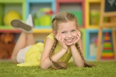 Close up portrait of cute smiling girl. With plaits lying on floor stock images